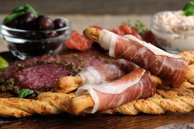 Przekąski antipasto z salami grissini owinięte oliwkami prosciutto i pastą serową na drewnie