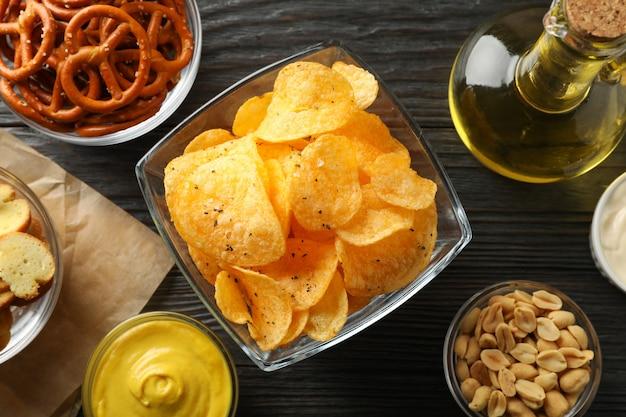 Przekąski do piwa, chipsy ziemniaczane, orzechy piwne, sosy, oliwa z oliwek na drewnie, miejsce na tekst. zbliżenie