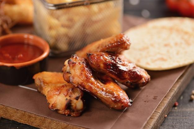 Przekąski do piwa. smażone skrzydełka z kurczaka, frytki, krążki cebuli, ser w cieście i suszone mięso. na drewnianej desce