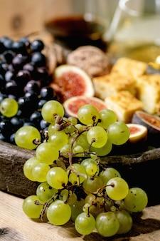 Przekąski do wina z różnymi winogronami, figami, orzechami włoskimi, chlebem, miodem i kozim serem na talerzu ceramicznym, podawane z kieliszkami czerwonego i białego wina na starym drewnianym stole. ścieśniać
