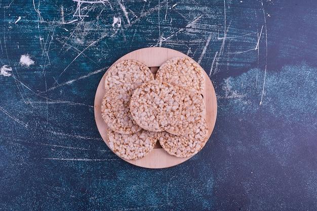 Przekąski i krakersy w drewnianym półmisku, widok z góry.