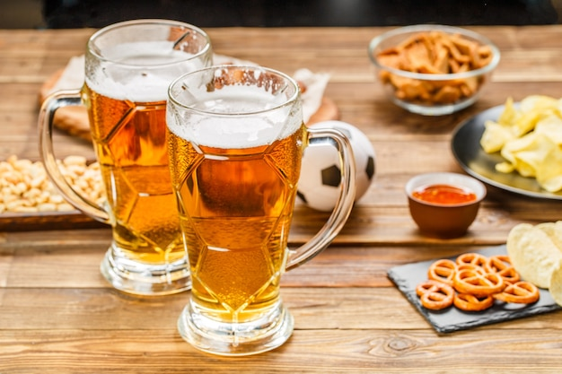 Przekąski i piwo na stole na imprezę piłkarską i oglądanie meczu piłki nożnej.