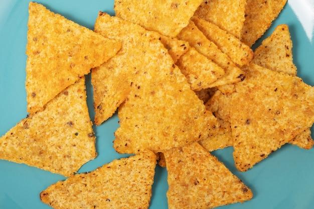Przekąski na imprezę. pyszne meksykańskie chipsy kukurydziane nachos na niebieskim talerzu