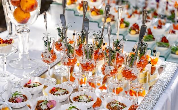 Przekąski w małych okularach na białym stole niewyraźne tło. stół imprezowy. koncepcja gastronomiczna.