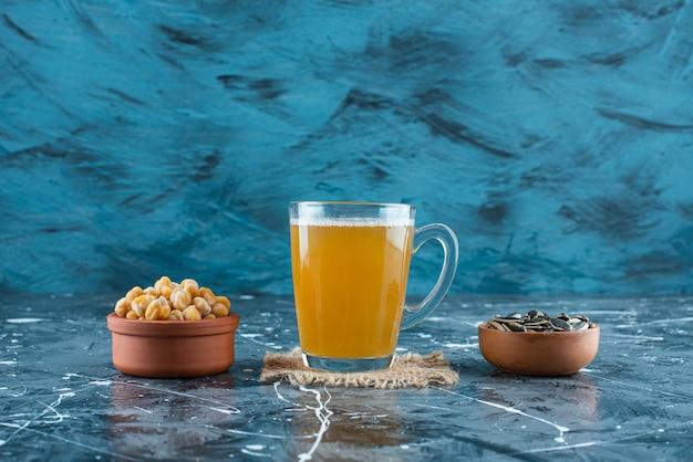 Przekąski w miskach obok szklanki piwa na fakturze, na niebieskim stole.