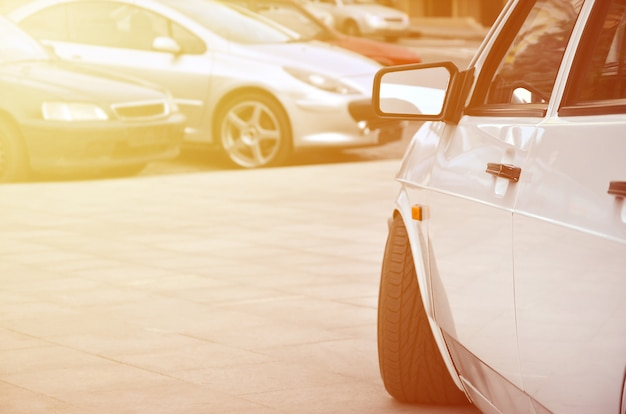 Przekątna widoku białego błyszczącego samochodu, który stoi na kwadracie szarych płytek