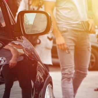 Przekątna widoku czarnego błyszczącego samochodu z białymi kółkami, który stoi na kwadracie szarych płytek