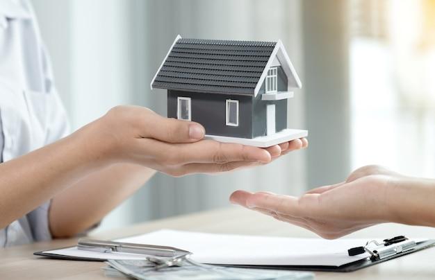 Przekaż agentowi nieruchomości, trzymaj model domu i wyjaśnij kobiecie kupującej umowę biznesową, wynajem, kupno, hipotekę, pożyczkę lub ubezpieczenie domu.