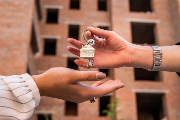 Przekazanie kluczy do domu między pośrednikiem a nowym właścicielem. koncepcja sprzedaży