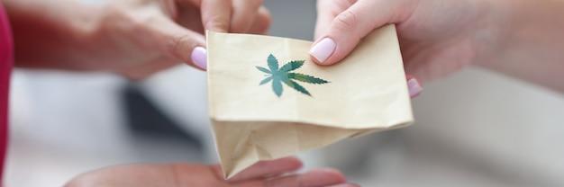 Przekazanie papierowej torby ze znakiem marihuany