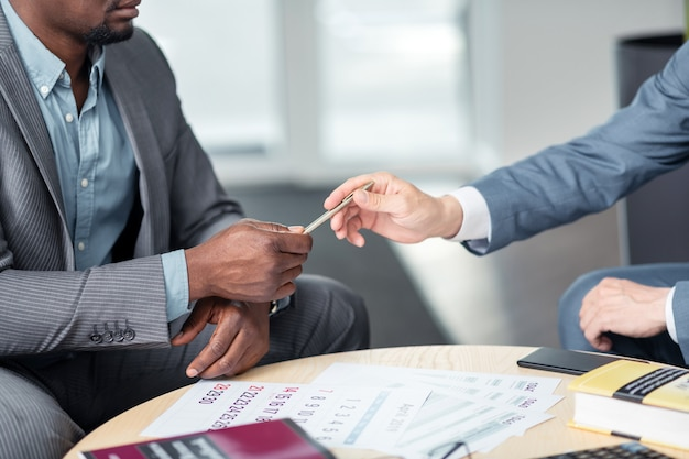 Przekazanie pióra. ciemnoskóry biznesmen wręcza pióro koledze podczas podpisywania umowy