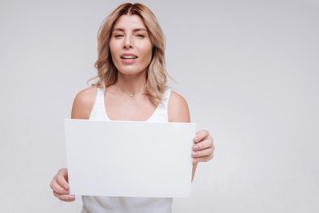 Przekazywanie wiadomości. hipnotyczna, zakrzywiona, oddana kobieta demonstruje białą kartkę papieru