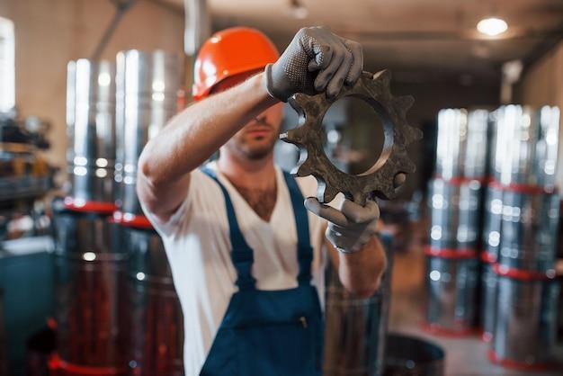Przekładnia mechaniczna. mężczyzna w mundurze pracuje nad produkcją. nowoczesna technologia przemysłowa.