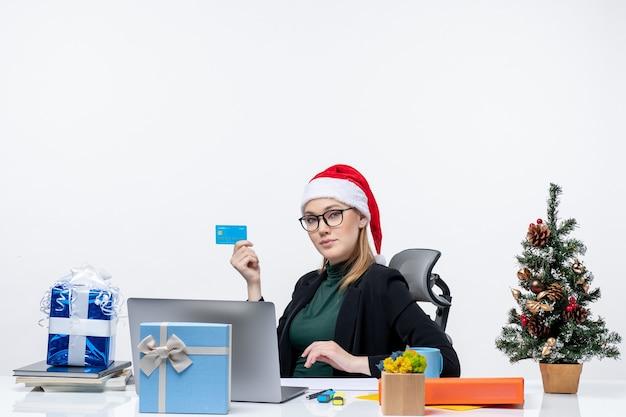 Przekonana, atrakcyjna kobieta w kapeluszu świętego mikołaja i okularach siedzi przy stole i trzyma kartę bankową w biurze