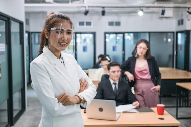 Przekonana, azjatycka kobieta kierownik noszenie osłony twarzy uśmiechnięta i skrzyżowana ramiona z kolegami z biura pracującymi w biurze na tle