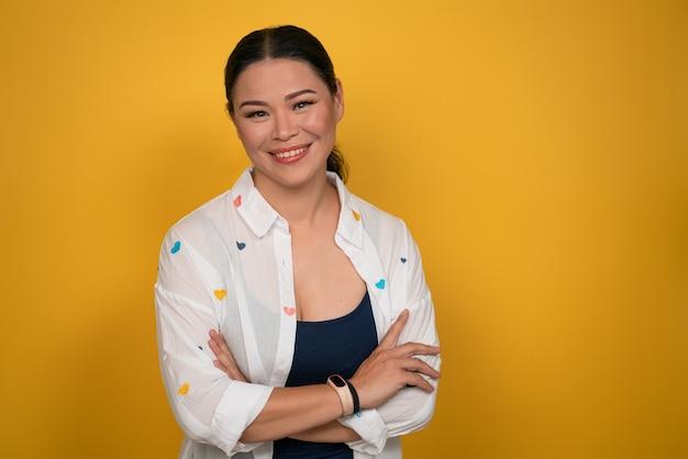 Przekonana, azjatycka kobieta uśmiecha się stojąc skrzyżowanymi rękami na żółtym tle. skopiuj miejsce.