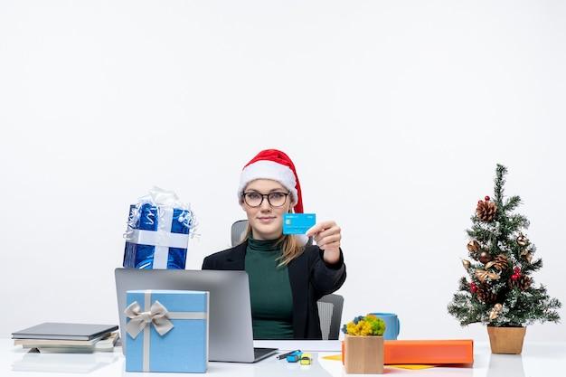 Przekonana biznesowa kobieta w kapeluszu świętego mikołaja i noszeniu okularów siedzi przy stole trzymając prezent na boże narodzenie i kartę bankową na białym tle
