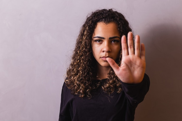 Przekonana, czarna kobieta protestuje przeciwko dyskryminacji rasowej na białym tle na żółtym tle - młoda zróżnicowana afrykańska kobieta pokazująca gest czarnego życia materii - zatrzymaj rasizm, koncepcja praw człowieka