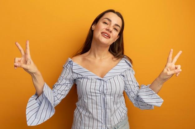 Przekonana, dość kaukaski kobieta gestykuluje ręką znak zwycięstwa dwiema rękami na pomarańczowo
