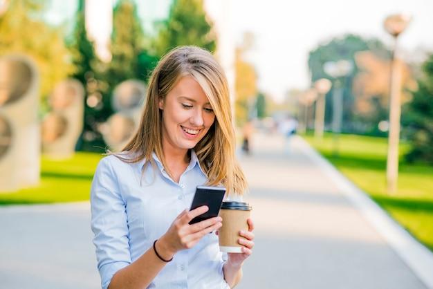 Przekonana kobieta czytanie informacji o nowościach finansowych podczas spaceru w korytarzu firmy podczas przerwy w pracy, pomyślne businesswoman pisania wiadomości tekstowych jej klienta, podczas gdy idzie z sekretarzem biura