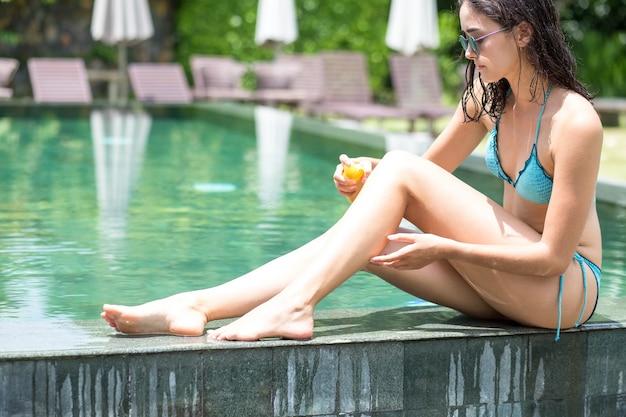 Przekonana kobieta stosowania kremu przeciwsłonecznego na krawędzi basenu