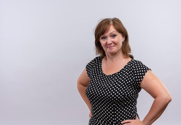 Przekonana kobieta w średnim wieku kładzie ręce na talii na odosobnionej białej ścianie z miejsca na kopię