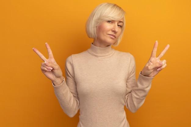 Przekonana, ładna blondynka słowiańska gestykuluje ręką znak zwycięstwa dwiema rękami na pomarańczowo