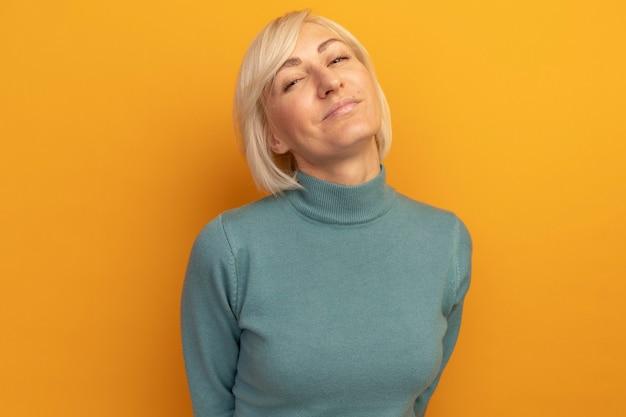 Przekonana, ładna blondynka słowiańska kobieta patrzy z przodu na białym tle na pomarańczowej ścianie