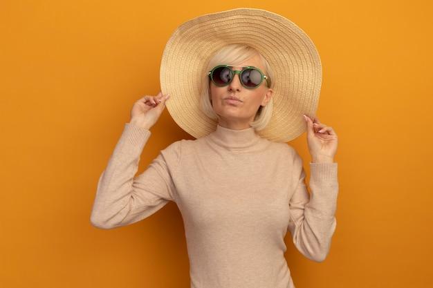 Przekonana, ładna blondynka słowiańska kobieta w kapeluszu plażowym w okularach przeciwsłonecznych stoi na pomarańczowo