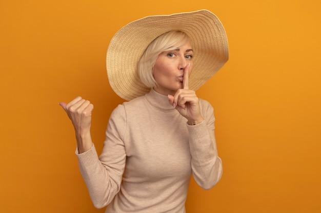Przekonana, ładna blondynka słowiańska kobieta z kapeluszem na plaży robi gest ciszy wskazując na bok na pomarańczowo