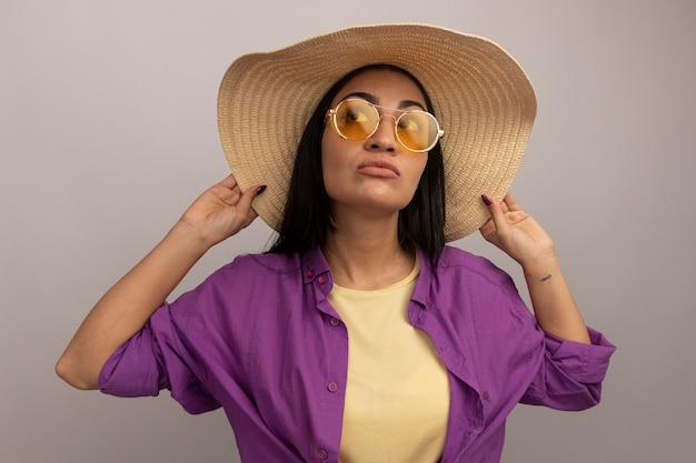 Przekonana, ładna brunetka kaukaska dziewczyna w okularach przeciwsłonecznych z kapeluszem plażowym patrzy z boku na biały