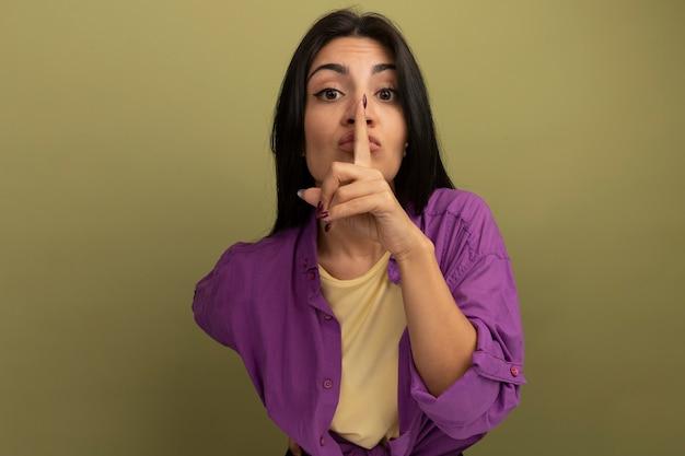 Przekonana, ładna brunetka kobieta robi gest ciszy patrząc z przodu na białym tle na oliwkowej ścianie