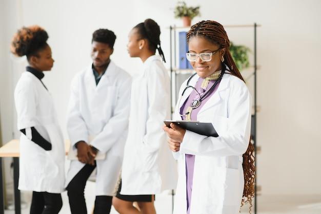 Przekonana, lekarz kobiet przed zespołem, patrząc na kamery uśmiechnięty, wielorasowy zespół z czarnym lekarzem kobietą