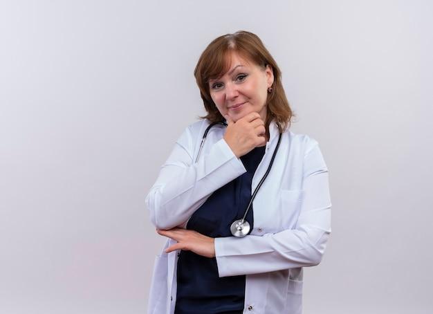 Przekonana, lekarz kobieta w średnim wieku, ubrana w szlafrok i stetoskop, kładąc rękę na brodzie na odosobnionej białej ścianie z miejsca na kopię