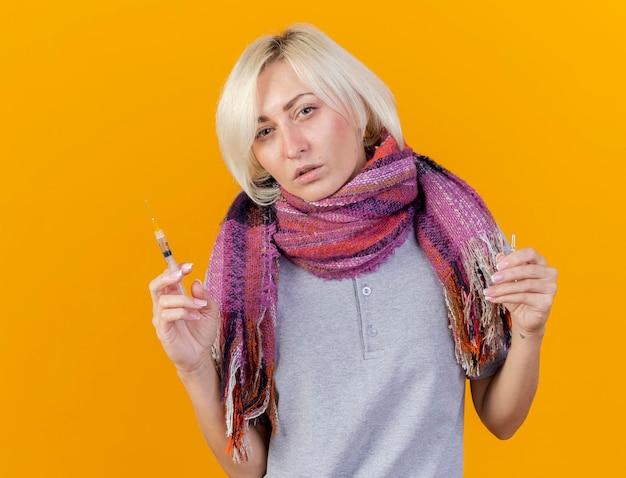 Przekonana, młoda blondynka chora słowiańska kobieta na sobie szalik trzyma strzykawkę