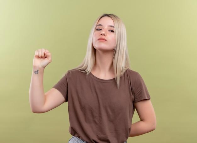 Przekonana, młoda blondynka, podnosząc pięść i kładąc rękę za plecami na odosobnionej zielonej przestrzeni
