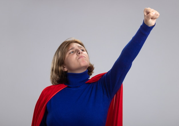 Przekonana, młoda blondynka superwoman w czerwonej pelerynie, podnosząc pięść, patrząc na to na białym tle na białej ścianie