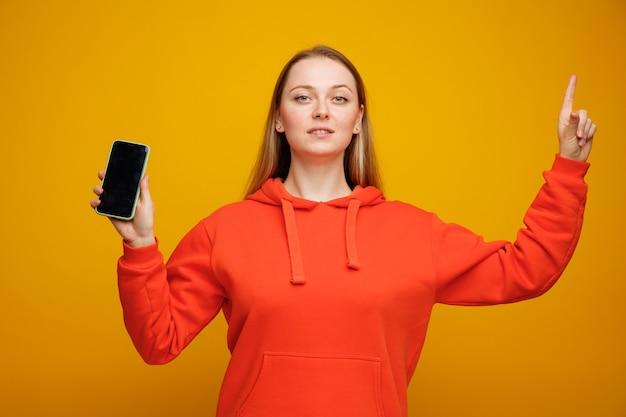 Przekonana, młoda blondynki kobieta trzyma telefon komórkowy skierowaną w górę