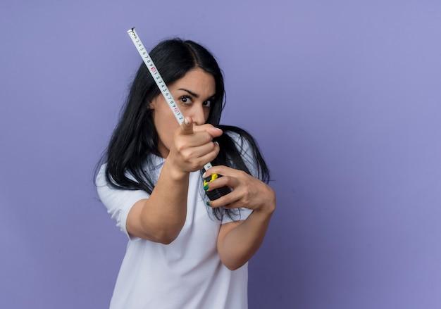 Przekonana, młoda brunetka kaukaski dziewczyna trzyma centymetrem i punkty na białym tle na fioletowej ścianie