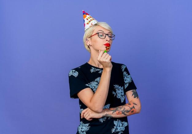 Przekonana, młoda dziewczyna blonde party w okularach i czapkę urodziny trzymając dmuchawę patrząc w dół na białym tle na fioletowym tle z miejsca na kopię