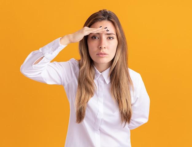 Przekonana, młoda dziewczyna dość kaukaski trzyma dłoń na czole, patrząc na kamery na pomarańczowo
