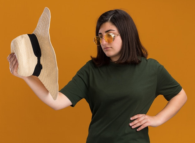 Przekonana, młoda dziewczyna dość kaukaski w okularach przeciwsłonecznych, trzymając i patrząc na kapelusz plażowy na białym tle na pomarańczowej ścianie z miejsca na kopię