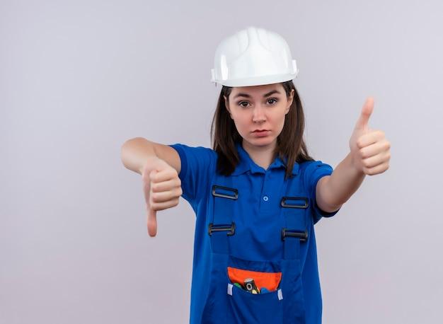Przekonana, młoda dziewczyna konstruktora z białym hełmem ochronnym i niebieskim mundurem kciuki w dół i kciuki w górę na odosobnionym białym tle z miejsca na kopię