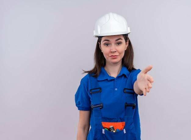 Przekonana, młoda dziewczyna konstruktora z białym hełmem ochronnym i niebieskim mundurem trzyma rękę na na białym tle z miejsca na kopię