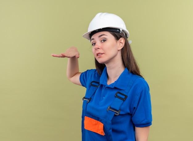 Przekonana, młoda dziewczyna konstruktora z białym hełmem ochronnym i niebieskim mundurem trzyma rękę prosto i patrzy na kamerę na odosobnionym zielonym tle z miejsca na kopię