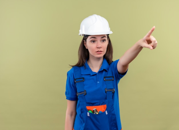 Przekonana, młoda dziewczyna konstruktora z białym hełmem ochronnym i niebieskim mundurem wskazuje na pojedyncze zielone tło z miejsca na kopię