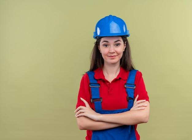 Przekonana, młoda dziewczyna konstruktora z niebieskim hełmem ochronnym skrzyżowanymi rękami na na białym tle zielonym tle z miejsca na kopię