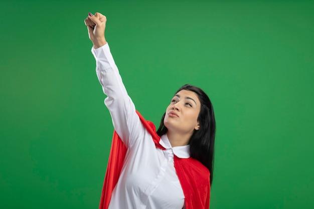 Przekonana, młoda dziewczyna superbohatera kaukaski, podnosząc pięść w górę i pokazuje znak zwycięstwa patrząc w górę na białym tle na zielonym tle z miejsca na kopię