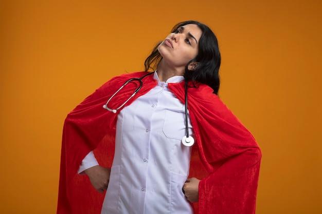 Przekonana, młoda dziewczyna superbohatera patrząc na sobie szlafrok medyczny ze stetoskopem, kładąc ręce na biodrze na białym tle na pomarańczowej ścianie