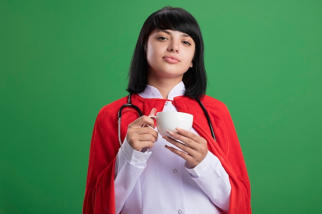 Przekonana, młoda dziewczyna superbohatera w stetoskopie z medycznym szlafrokiem i płaszczem, trzymając filiżankę herbaty na białym tle na zielonej ścianie